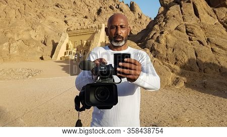 Egypt, Sharm El Sheikh - March 30, 2020. An Adult Black Egyptian Videographer With A Sony Camcorder