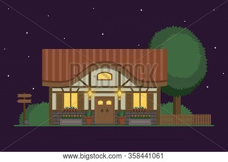 Half-timbered Cottage With Light In The Windows And Shining Lanterns At Nigh. Summer House With Tree