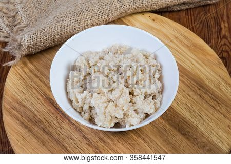 Barley Porridge Made With Crushed Barley Grits In The White Bowl On The Wooden Serving Board