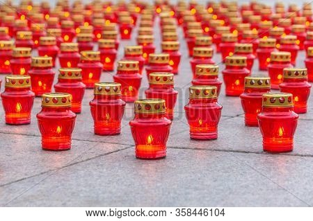 Burning Candles In Red Lanterns On Granite Slabs Background. Burning Lanterns To Honor Dead People.