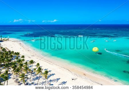 Aerial Drone View Of Beautiful Caribbean Tropical Beach With Straw Umbrellas, Palms And Boats. Bavar