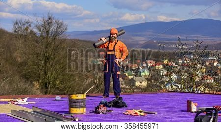 Confident Worker. Man Inspecting Damaged Roof. Qualified Builder Installing Roof Tile. Construction