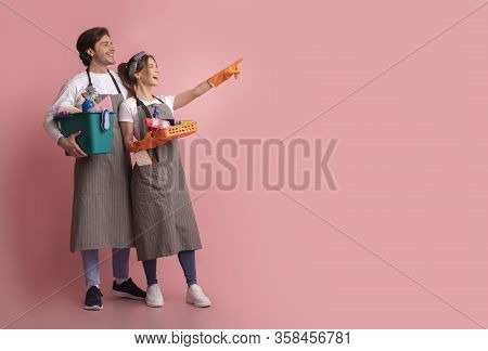 Housecleaning Service Concept. Excited Couple With Cleaning Supplies In Hands Looking And Pointing A