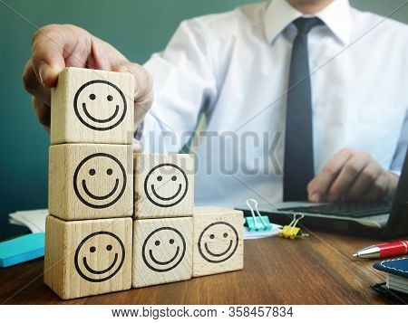 Good Rating In The Customer Satisfaction And Evaluation Concept. Businessman And Cubes.