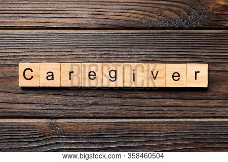 Caregiver Word Written On Wood Block. Caregiver Text On Wooden Table For Your Desing, Top View Conce