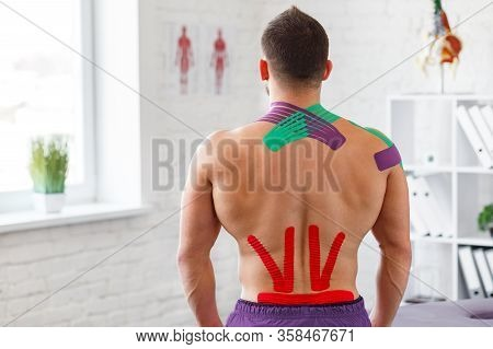 Kinesiology Taping. Physical Therapist Applying Kinesiology Tape To Patient Back. Therapist Treating