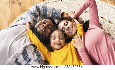 Family Evening At Home Multiracial Family. Daughter Hugging Parents