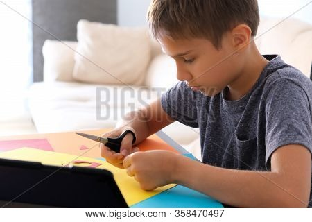 Education, Paper Crafts For Kids. Child Cutting Colored Paper With Scissors. Boy Looking Video Tutor