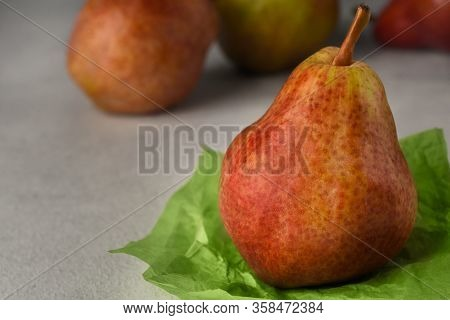 Red Ripe Pears On A Light Background. A Pear On A Piece Of Crumpled Green Wrapping Paper And Three P