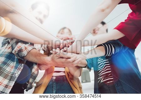 Co-working Startup Business Team And Teamwork Concept. Young Team Putting Hands Up In Creative Offic