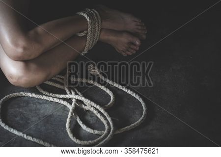 Feet Of A Missing Kidnapped, Abused, Hostage, Victim Woman Tied Up With Rope, Victims Of Human Traff