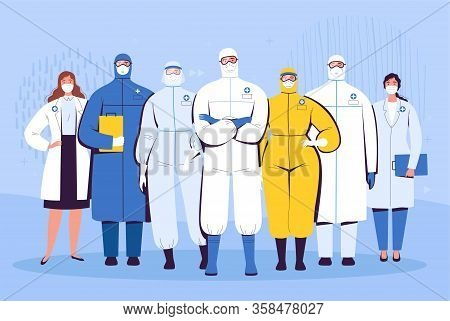 A Group Of Doctors In Protective Suits, Glasses And Medical Masks Are Standing Next To Each Other. T