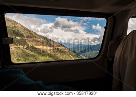 Road Trip In The Mountains. View From Car Side Window, With Real Motion Blur On The Road At The Bott