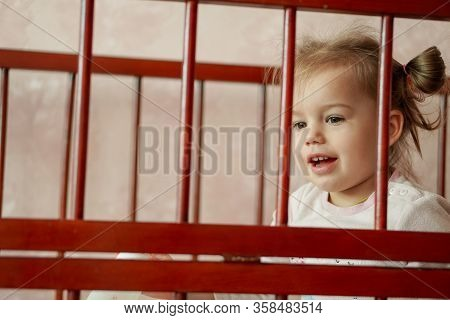 Little Beautiful Girl Dressed In Pajamas Sits In A Cradle. A Baby In A Pink Pajamas Sits In A Cot