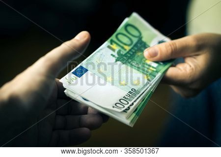 Close-up Of Person Hand Giving Money To Other Hand. Transfer Of Euro Banknotes