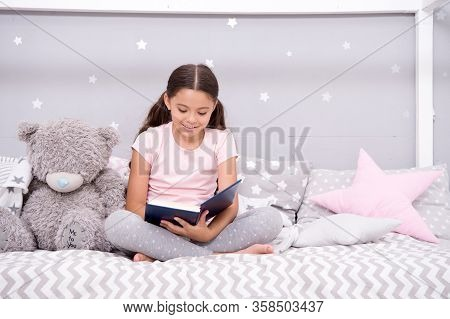 Read To Me. Little Girl Read Story To Teddy Bear. Small Kid Read Book In Nursery. Literature And Lib