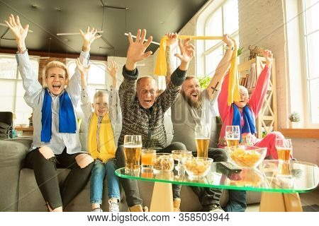 Excited Family Watching Football, Sport Match At Home. Grandparents, Parents And Kid Cheering For Fa