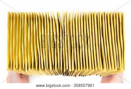 Huge Stack Of Yellow Mailing Envelopes In Hands, Top View, Isolated On White.