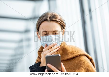 Young And Depressed Woman In Face Mask Worried Reading Bad News On A Smart Phone At A Public Transpo