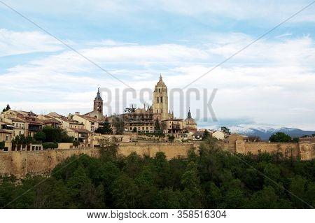 Surrounding Wall Of Old Town And Cathedral Of Segovia Against Blue Cloudy Sky And Snowy Guadarrama M