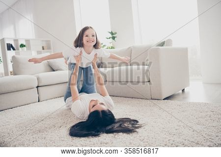 Photo Of Pretty Funny Little Girl Young Mommy Holding Daughter Hands Above Floor Having Fun Pretendi