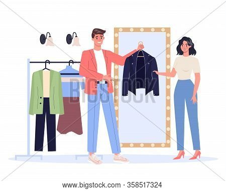 Young Male Fashion Stylist Holding A Leather Jacket For The Woman.