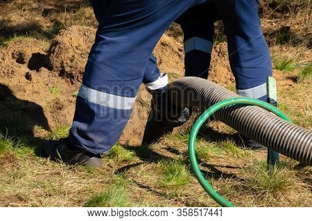 Man Worker Holding Pipe, Providing Sewer Cleaning Service Outdoor. Sewage Pumping Machine Is Unclogg