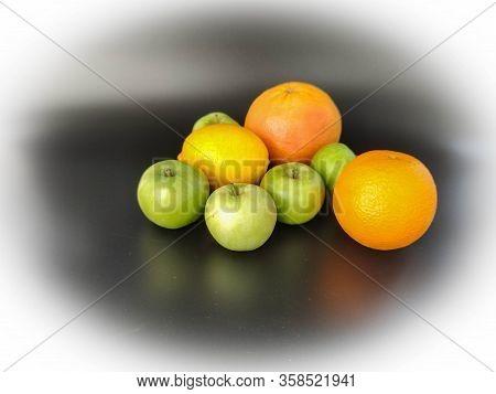 Whole Fruits Green Apples, Orange, Grapefruit And Lemon On Black Background. Concept - Vegetarian An