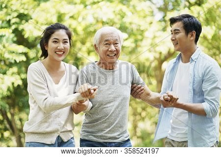 Young Asian Couple Helping Father Stand Up And Walk Outdoors In Park