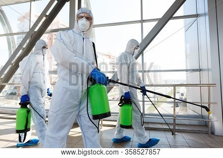 Professional Workers In Hazmat Suits Disinfecting Indoor Accommodation, Pandemic Health Risk, Corona