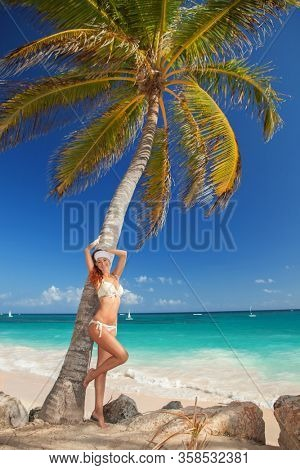 Fashion woman walking on the beach. Happy beach lifestyle. White sand, blue sky and crystal sea of tropical beach. Vacation at Paradise. Ocean beach relax, travel to ocean