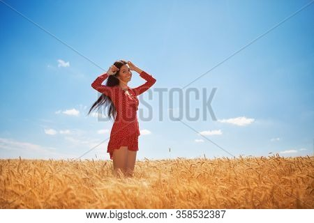 Happy woman enjoy the life in the field. Nature beauty, blue sky,white clouds and field with golden wheat. Outdoor lifestyle. Freedom concept. Woman walk in summer field