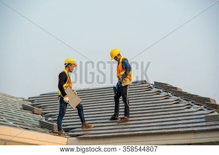 Roofer Working On Roof,professional Roofer Are Installing New Roof On Top Roof Of Modern House.