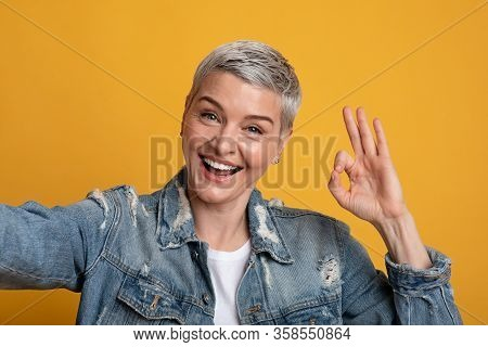 All Is Ok. Cheerful Middle-aged Woman Taking Selfie And Showing Okay Gesture While Posing Over Yello