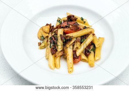 Spaghetti aglio e olio, pasta with dried chili and bacon. Italian cuisine.