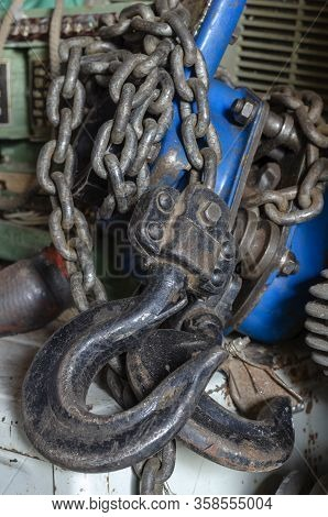 Hook And Chain Of An Old Hand Hoist. Used Hand Lifting Tool. Industrial Topics. Selective Focus. Eye