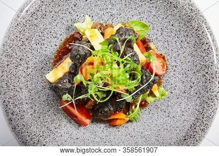 Chicken hearts in black tempura with vegetables. Roasted meat with cut tomatoes and garden cress top view. Asian cuisine, japanese recipe. Delicious restaurant dish served with greenery