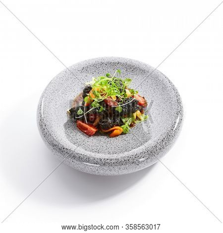 Chicken hearts in black tempura with vegetables. Roasted meat with cut tomatoes and garden cress side view. Asian cuisine, japanese recipe. Delicious restaurant dish served with greenery