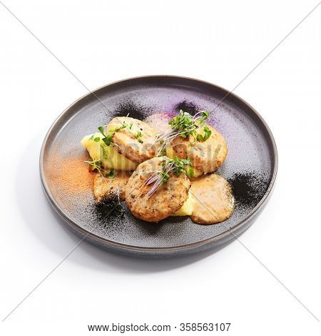 Fishcakes with garden cress side view. Delicious filleted fish with greenery on tray. Croquette seafood with aromatic sauce. Restaurant dish, culinary presentation. Food composition