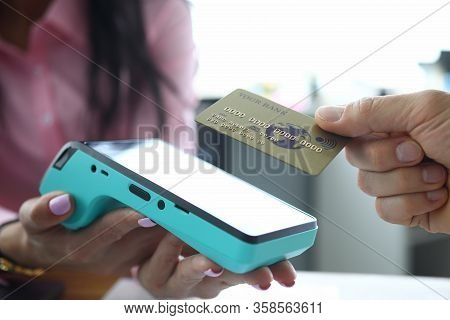 Man Holds Contactless Credit Card To Terminal. Payment For Goods And Services Via Internet. Banking