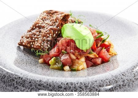 Tuna tartare closeup view. Chopped fish and crackers with seasonings. Tasty seafood with greenery, vegetable and bread. Haute cuisine, delicious restaurant dish. Food composition, culinary recipe