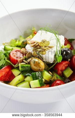 Greek salad in white bowl. Sliced fresh vegetables and feta cheese. Served traditional Greece cuisine. Cut raw tomatoes, cucumbers with olive oil in plate. Restaurant food portion close up