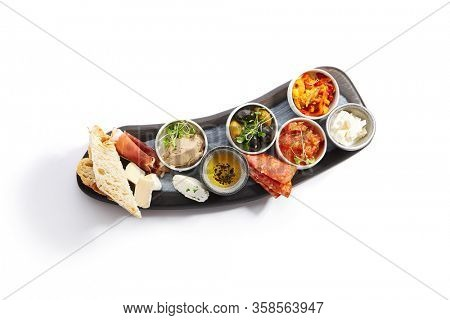 Wooden tray with snacks top view. Olives, burrata, jamon with pear. Bowls with liver pate, honey and cheese. Camembert, chorrizo, baked peppers and chopped tomatoes. Tasty ciabatta
