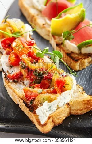 Tasty bruschetta with fish and baked peppers. Roasted italian bread with tuna and avocado. Delicious snacks served with greenery on wooden tray. Food composition, culinary presentation