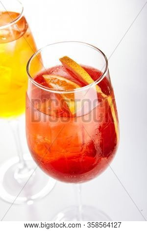 Rose Spritz cocktail. Alcohol soft drinks in glasses side view. Refreshment beverage with rose lemonade in drinkware. Exotic summer beach cocktail portions with crushed ice in glassware
