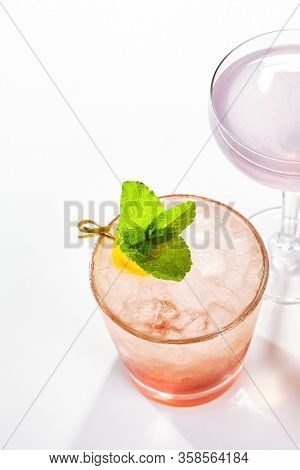 Bramble cocktail close up. Alcohol strong drink side view. Refreshment beverage with dry gin, lemon juice and violet liqueur. Cocktail with crushed ice, citrus and mint leaves in glassware