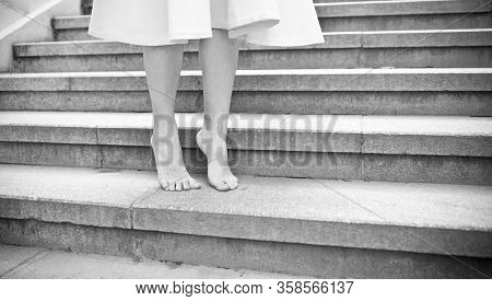 Balck And White Picture Of Young Woman Walking Barefoot Outdoors. Close Up Low Angle Side View Of Fe