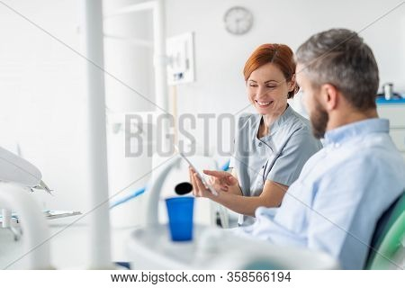 Side View Of Dentist Talking To Man In Dentist Surgery, A Dental Check-up.