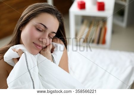 Girl Sitting On White Bed With Closed Eyes Resting. Relaxation Comfortable Pleasant Bed In Your Home