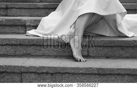 Attractive Slim Barefoot Legs And Feet Of Young Woman In Dress On Picture. Female Model Sit On Stepa
